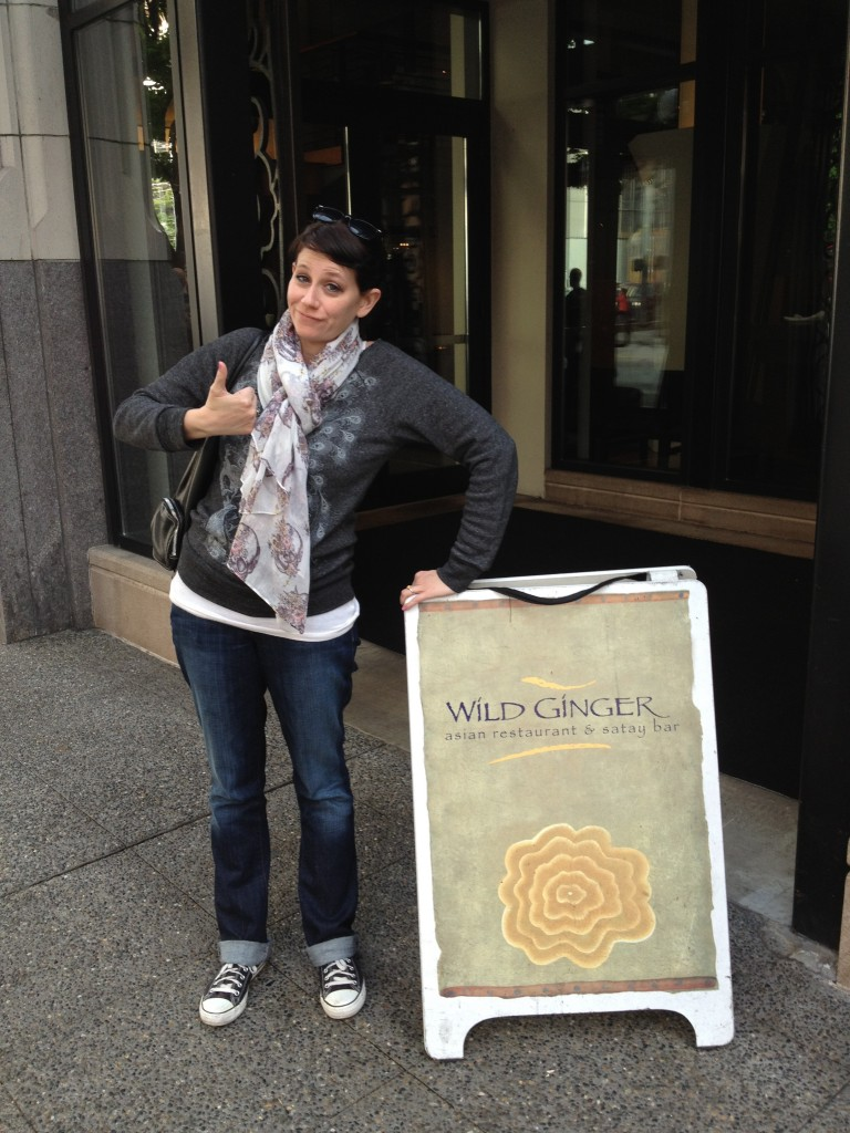 Erica posing with a thumbs up sign outside of Wild Ginger in Seattle, WA, one of the best gluten-free friendly restaurants in Seattle