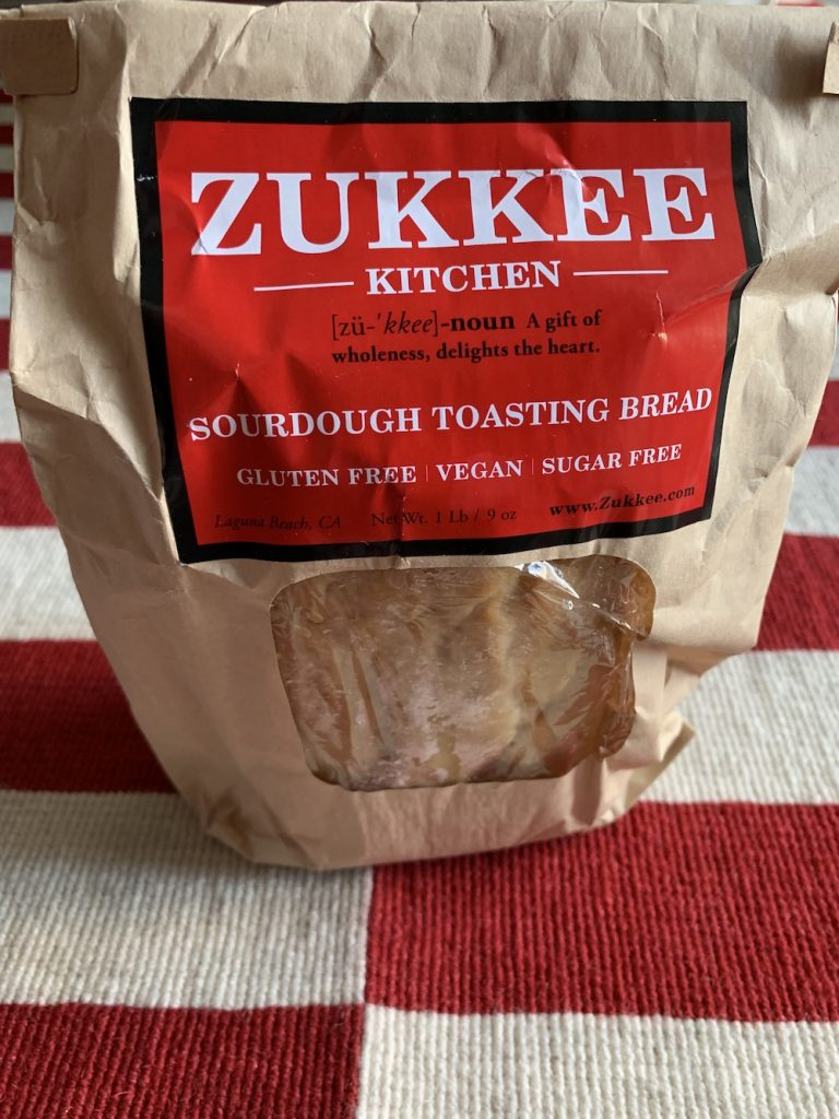 Loaf of Zukkee Kitchen sourdough bread in packaging on a rug