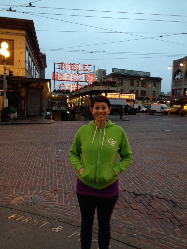 Image of Erica wearing a gluten-free branded green sweatshirt, Seattle Pike Place Market Center behind her, early morning
