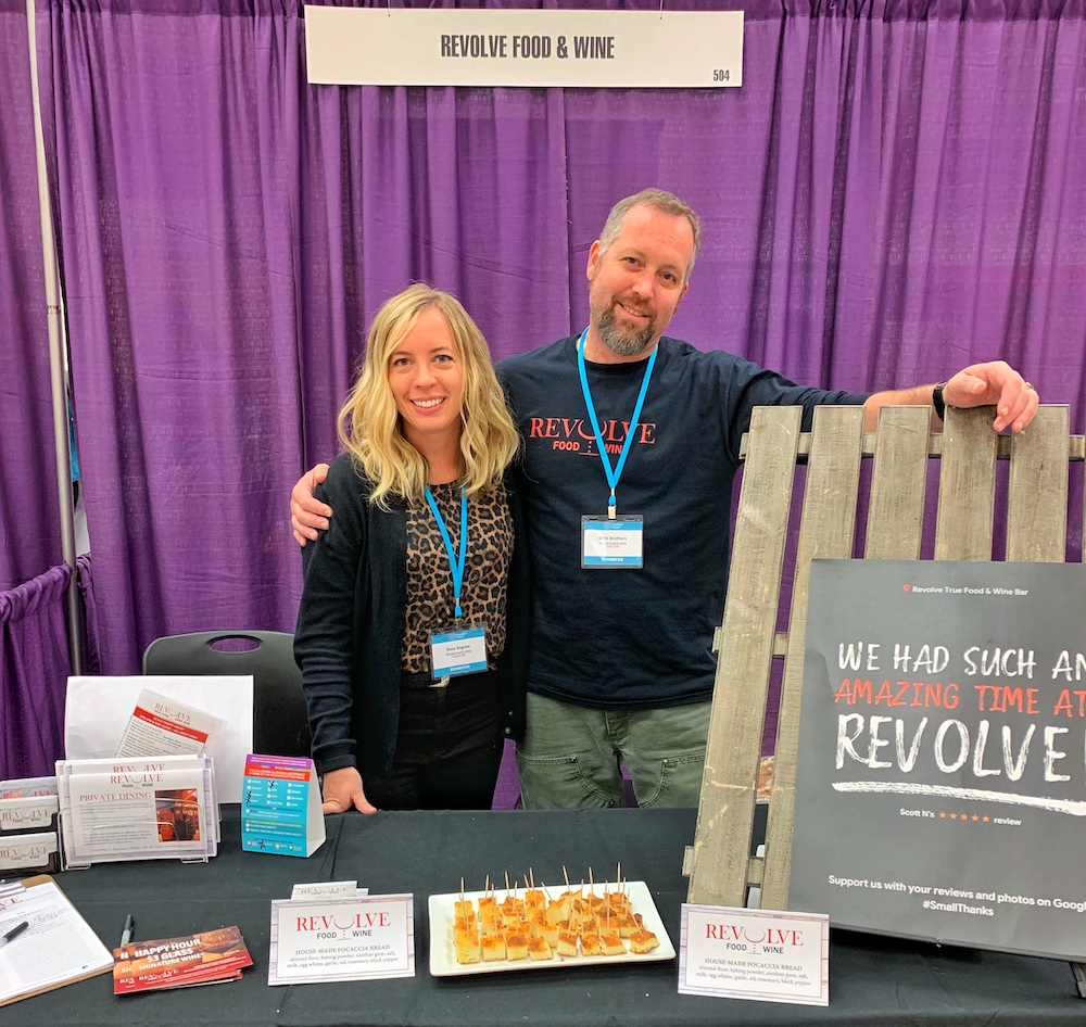 Two owners hugging at the Revolve Food & Wine booth at the Seattle Washington Nourished Festival in 2019, a top gluten-free restaurant in Seattle metro area, just outside the city