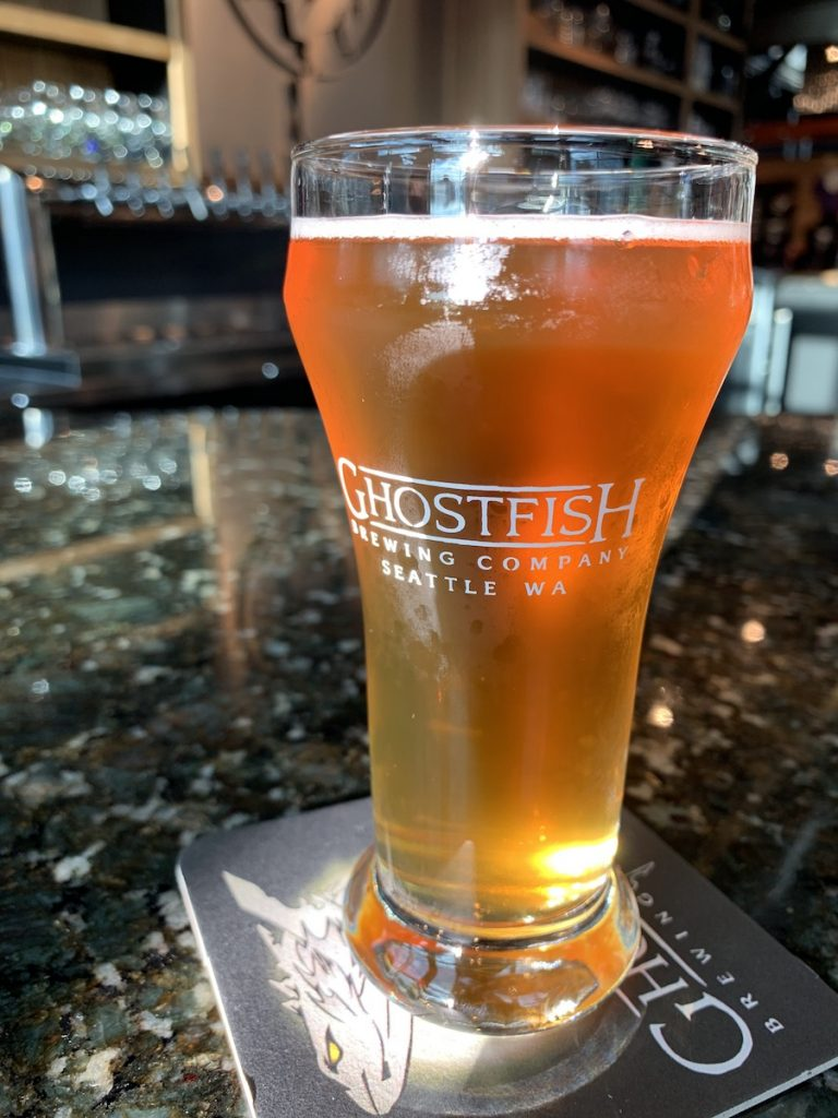 Photo of pint glass of Ghostfish Brewing Company filled with beer at the Seattle brewery on a coaster