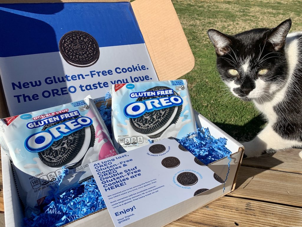 JoJo the cat by a box full of Gluten-Free OREO cookies